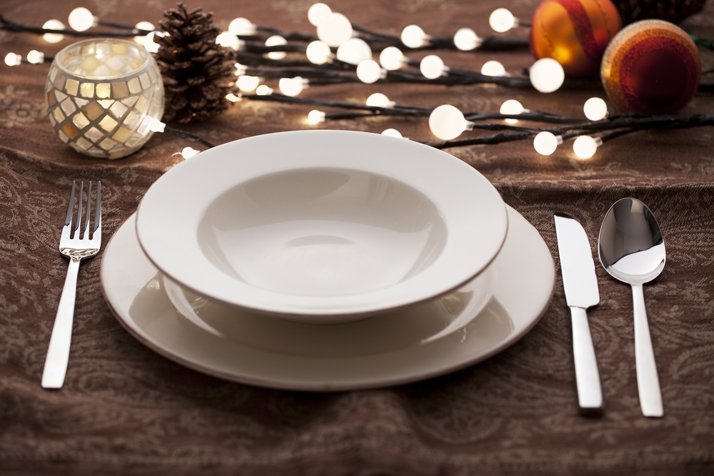 Beautiful, warm chritmas place setting with christmas lights and candle bowl